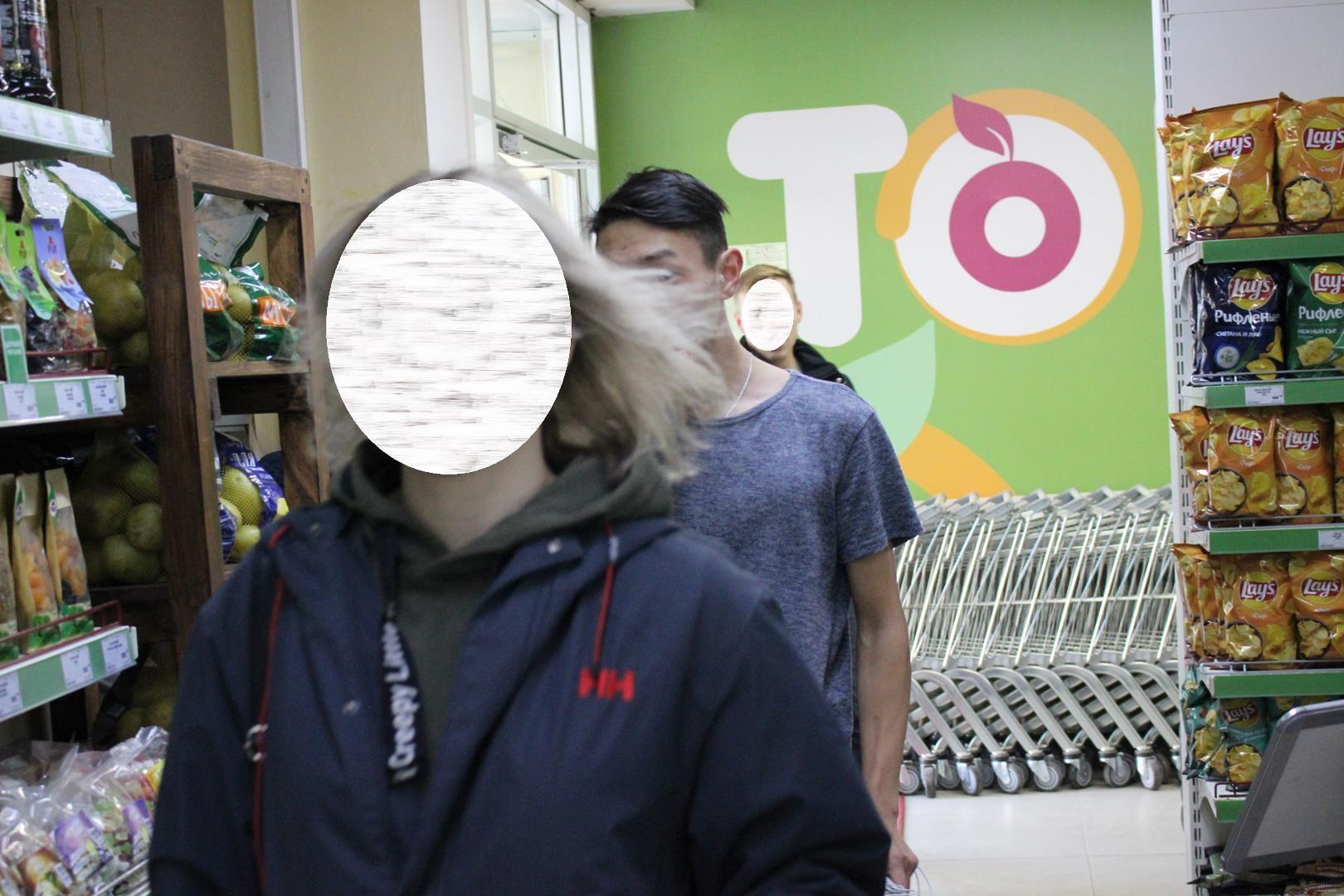 Несколько молодых людей пробегают мимо пункта охраны без масок
